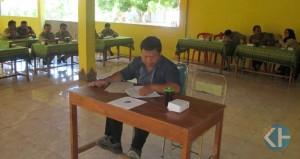 Rambadi sedang mengerjakan soal ujian Kabag Pembangunan Desa Terbah. Foto : Atmaja.