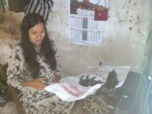 Istri Bowo sedang memotong karung goni yang akan dijahit. Foto : Atmaja