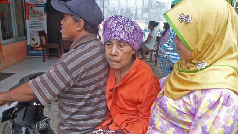 Mbah Supi menerima psks di atas motor. Foto : Sarwo