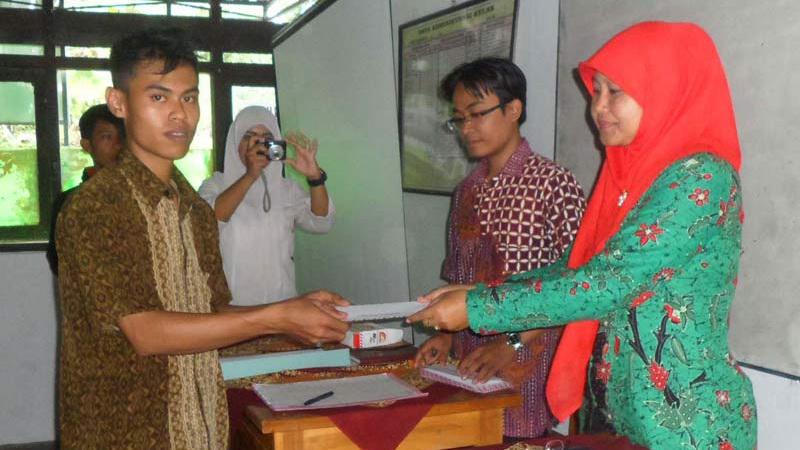 Kepala SMK Maarif Playen menyerahkan tanda kelulusan kepada siswa. KH/Sarwo.