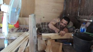Sunardi sedang menggergaji kayu untuk bahan sangkar burung. KH/Kandar