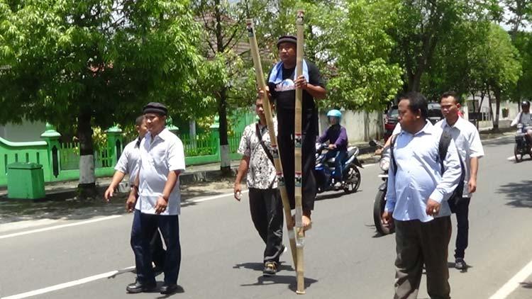 Sudarmoyo berjalan menggunakan Egrang menuju Rumah Dinas Bupati. KH/ Edo