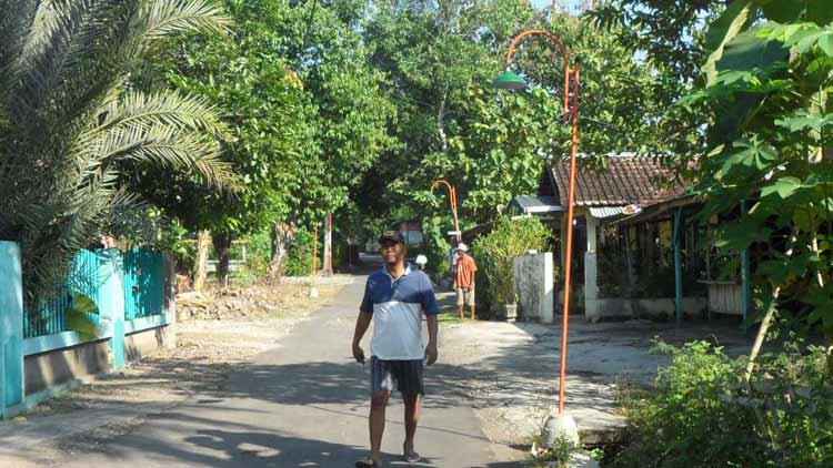 Warga Desa Playen gotong royong memasang lampu penerangan jalan. KH/ Sarwo