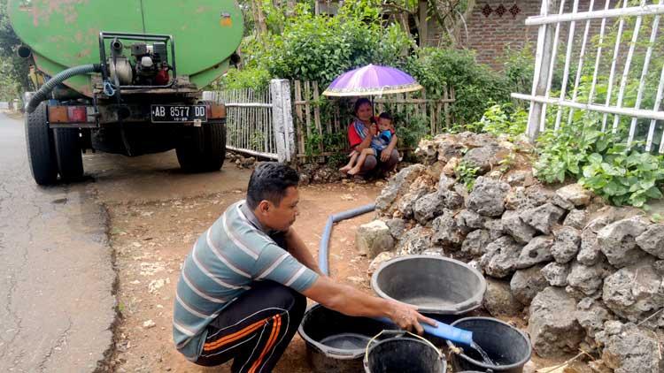 Warga menunggu sisa air yang tertahan di selang setelah dialirkan dari tangki ke bak tampungan air. KH/ Kandar