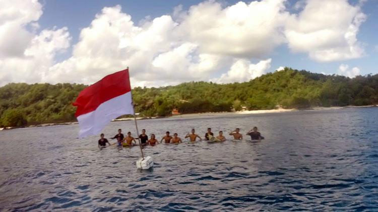 Anggota Wediombo Surf Society mengibarkan bendera di Laut Kawasan Pantai Wediombo. KH/ Rado