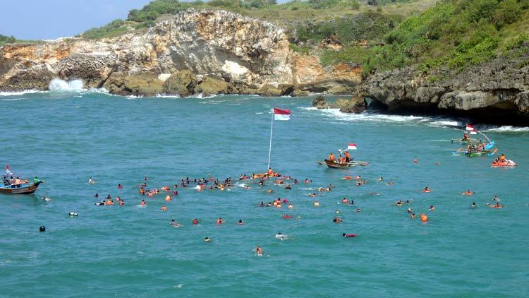 Pengibaran Bendera Merah Putih di laut kawasan Pantai Baron. KH/ Kandar.