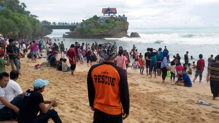 Seorang anggota Tim SAR memantau wisatawan yang sedang asyik bermain di Pantai Kukup. KH