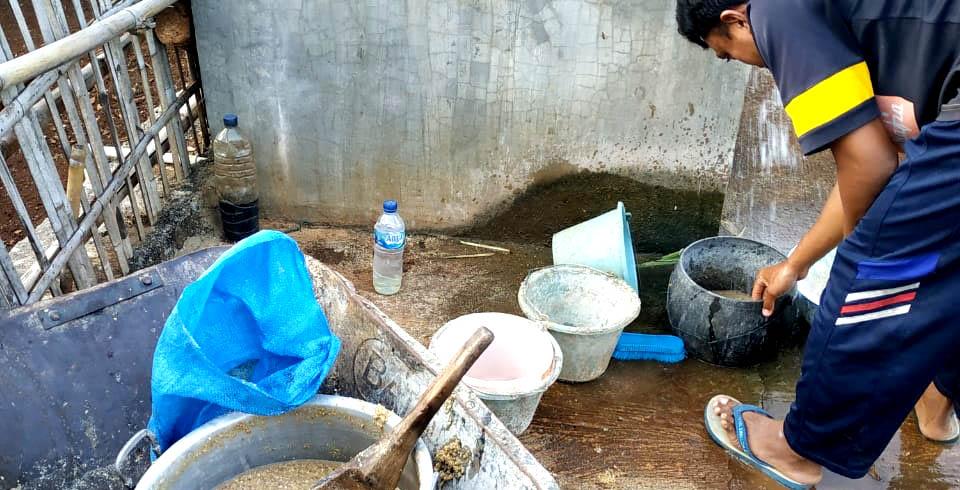 Imam sedang menyiapkan komboran untuk kambing.[Foto:Padmo]
