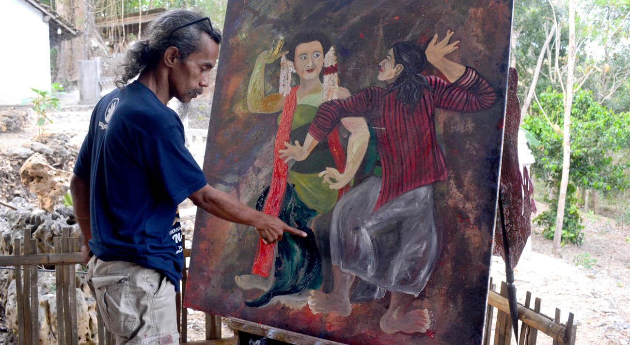 Bernard Wora Wari sedang menunjukkan lukisannya.[Foto:Padmo]